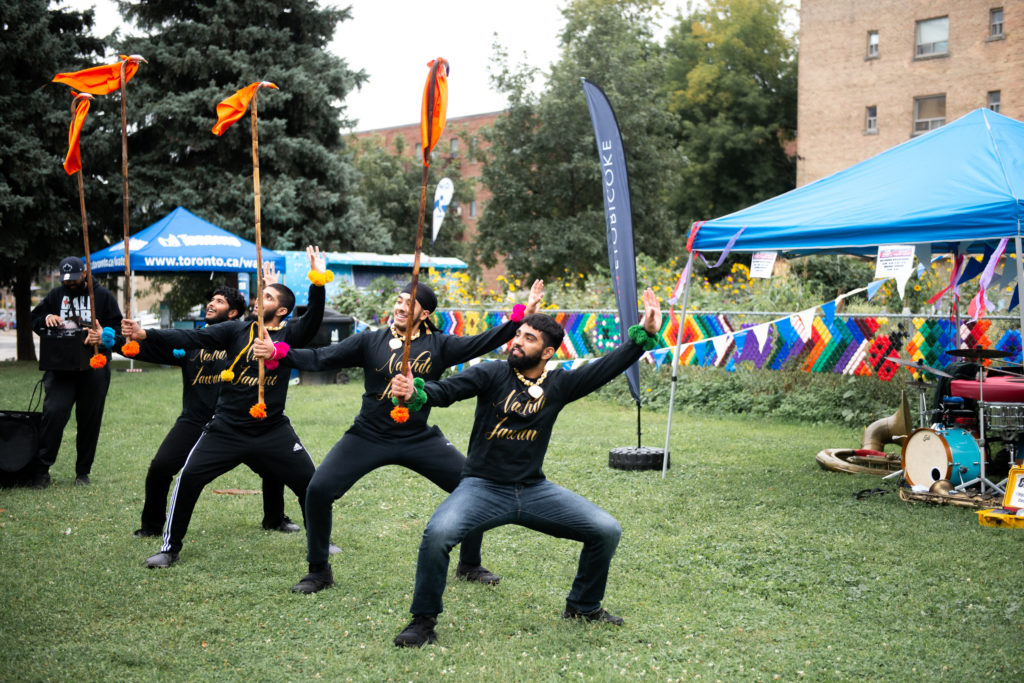 Dancers from Bhangra Dance Troupe Nachdi Jawani holding a pose, wearing all black and holding sticks with brightly coloured flags and pom poms